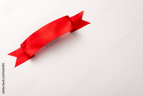 top view of red satin ribbon on white