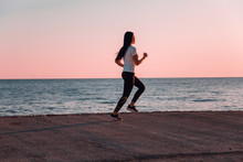 The Concept Of Sport And Running. Woman In Sportswear Running On The Track. In The Background, The Sea And The Horizon Line. Copy Space. Pink Sunset