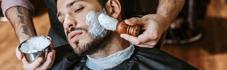 panoramic shot of barber applying shaving cream on face of handsome bearded man