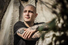 Young Attractive Stern Guy In Tattoos Sits On A Window Frame Of A Destroyed Building. Brutal Young Man With Tattoos On His Arms And Neck Sits On The Wall Of An Abandoned House. Bully, Bad Guy.