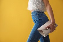 Woman In Jeans With Clutch Pur...