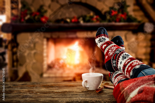 Spoed Foto op Canvas Europa Desk of free space and people legs with christmas socks.Home interior with fireplace and