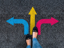 Woman Legs In Shoes Standing On Road With Three Direction Arrow Choices, Left, Right Or Move Forward