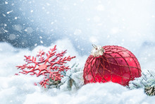 Red Christmas Ball On Snow With Fir Branches. Merry Xmas Concept