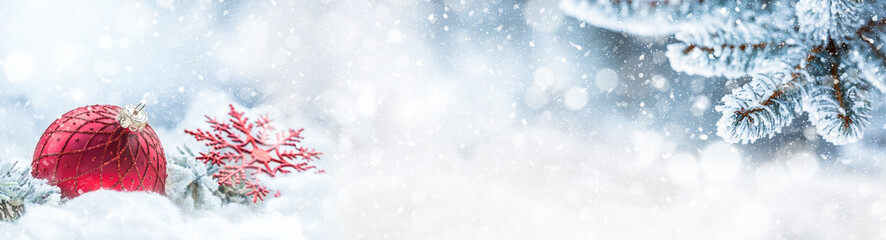 Red christmas ball on snow with fir branches. Merry Xmas concept - panoramic banner