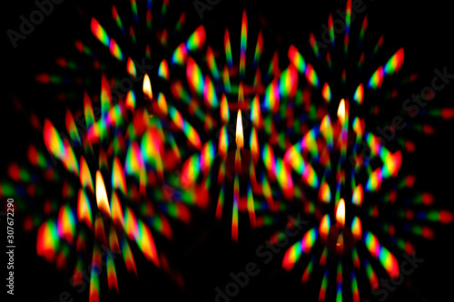 Fototapeta Flame of a candles surrounded by a halo of multi-colored glares, was photographed through two crossed diffraction gratings