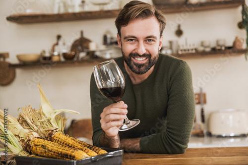 Fototapeta Smiling young man holding wineglass
