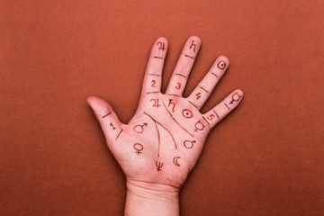 Person's left palm with drawn lines and chiromancy symbols