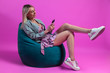 Leinwanddruck Bild - Beautiful blonde girl in a blue jacket and a purple sundress sits on a green bag chair with her cross leg on a pink background and chatted in social networks on the phone. Mobile and cell telephony.