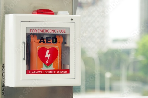 Fototapeta General view of a life saving defibrillator. Portable automated external defibrillator (AED) mounted on the wall in public restroom at airport. obraz