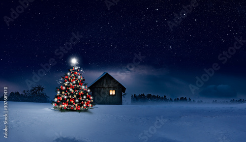 Fond de hotte en verre imprimé Nature Glänzend leuchtender Christbaum im Schnee bei einer Holzhütte mit leuchtendem Fenster