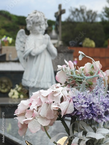 Scene in a graveyard: in the foreground, a bouquet of pink and purple artificial flowers Billede på lærred