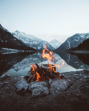 Campfire With Teapot In Front Of The Mountains At The Lake