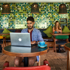 Handsome millennial indian man working in trendy coworking space