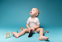 Little Girl Looks Up Holding Mother's Wallet In Her Hands. Around Scattered Dollars