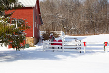 A Red Barn With A White Fenced In Area Full Of Snow With A Horse Statue In The Yard Decorated For Christmas