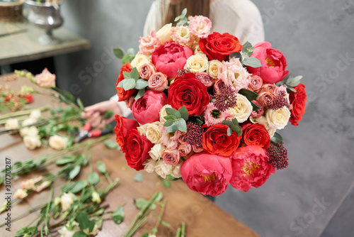 European floral shop concept. Florist woman creates red beautiful bouquet of mixed flowers. Handsome fresh bunch. Education, master class and floristry courses. Flowers delivery. © malkovkosta