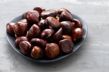 fresh chestnuts on dish on ceramic background