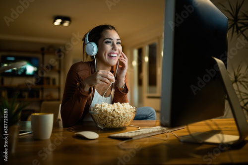 Fototapeta Young woman having fun while eating popcorn and watching movie on a computer in the evening. obraz