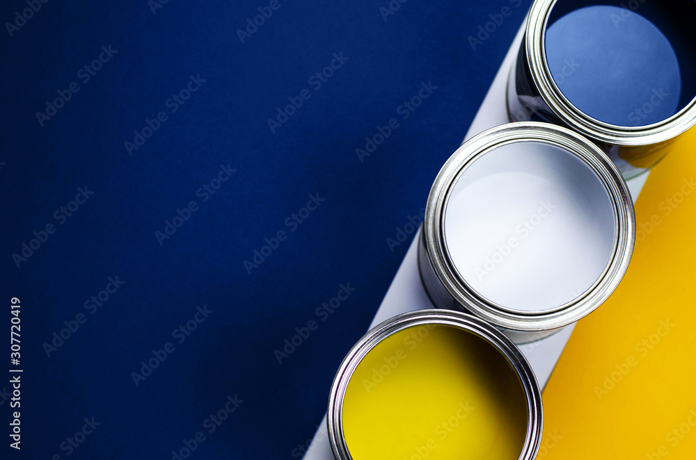 Fototapeta Cans of paint on a background of yellow and classic blue.