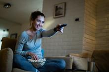 Happy Woman Using Remote Contr...