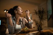Below View Of Woman With Eyes Closed Enjoying In A Taste Of Healthy Salad.