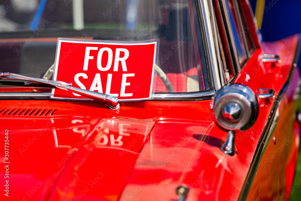 Fototapeta FOR SALE, red sign on classic antique American bright red car windscreen and chrome parts close up, during outdoor old cars show