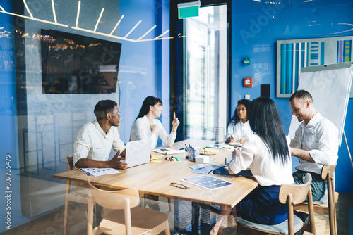 Fotografie, Tablou  Considerate multiethnic colleagues discussing graphs while sitting in office