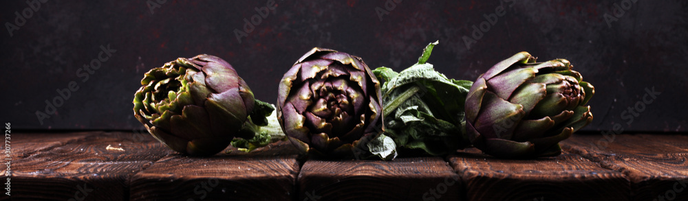 Fototapeta artichokes on rustic background. fresh raw organic artichoke flower.