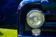 Bright Blue Old Classic Antique American Car Half Front, Left Side, Close Up On Glass Headlights And Signals Light Lamps