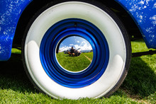 Vintage Classic American Bright Blue Car Wheels On The Grass, Close Up On The Steel Wheel Chrome Center And Whitewall Tire