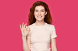 canvas print picture - Happy millennial red-haired woman looking at camera, showing ok gesture.