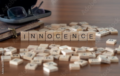 Photo  innocence the word or concept represented by wooden letter tiles