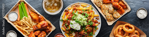 Slika na platnu top down photo of carne asada fries and buffalo chicklen wings