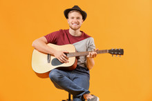 Handsome Man Playing Guitar On Color Background