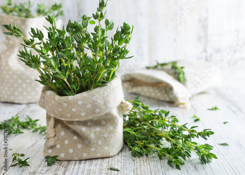 Fototapeta Fresh green thyme in decorative linen bag on an old wooden table. obraz