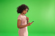 Leinwandbild Motiv Side view of young stylish woman on her smartphone on greenscreen