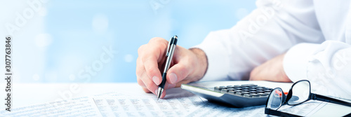 Fototapeta Business Man Using Pen And Calculator On Desk With Reading Glasses And Financial Report- Business Accounting Concept obraz
