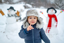 Merry Christmas And Happy New Year. Winter Portrait Of Little Boy Child In Snow Garden Make Snowman. Cute Kid - Winter Portrait. Winter Clothes For Kids.