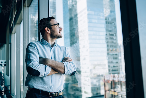 Contemplative male entrepreneur with crossed hands standing near office window view and feeling pondering during work day in company, Caucasian pensive corporate boss thoughtful looking away