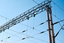 Power Electricity Wire For Trains Against Blue Sky. Close Up Of The Railway Electrification System