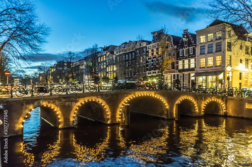 Amstedam, capital of Netherlands. Beautiful city of Amsterdam illuminated at dusk. Bicycles along the street and on the bridge over the canal.