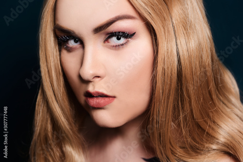 Fototapety, obrazy: Blonde with long hair looking at the camera. Professional makeup, beautiful eyebrows, white lenses. Looking vampires, bright eyes. Hair care. Blindinka on a black back