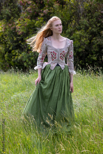 Carta da parati Red-haired 18th century woman in embroidered bodice and standing in long grass i