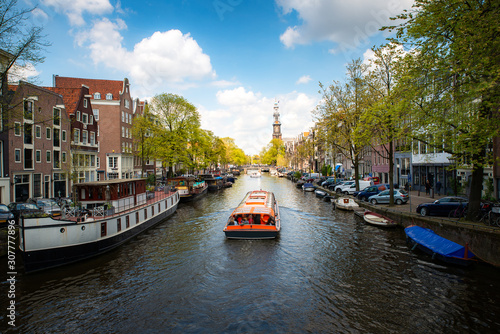 Photo Amsterdam canal with cruise ship with Netherlands traditional house in Amsterdam, Netherlands