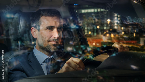 Fotografia An young handsome businessman driving a modern car in center of the city by night