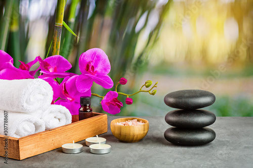 Fototapety Spa   hot-spa-stones-set-for-massage-treatment-orchid-flower-towels-candles-and-sea-salt-on-green