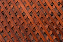 Brown Wooden Wall Lattice Background Texture.  Wooden Fence Cross Pattern. Crossing A Tree With Nails.