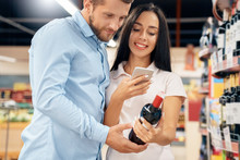 Daily Shopping. Couple In The Supermarket Together At Alcohol Department Choosing Wine Scanning Qr Code On Smartphone Looking For Info Joyful Close-up