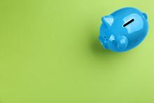 Blue Piggy Bank On Green Backg...